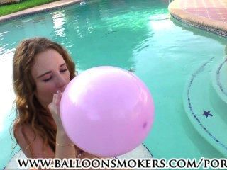 श्यामला किशोर पूल में बाहर गुब्बारे पॉप करने के लिए चल रही है