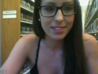 पुस्तकालय में चश्मे के साथ लड़की