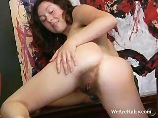 बालों वाली लड़की लुका स्ट्रिप्स और एक मेज पर masturbates