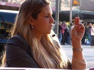 आउटडोर आंगन में सुंदर गोरा धूम्रपान की ओर रुख