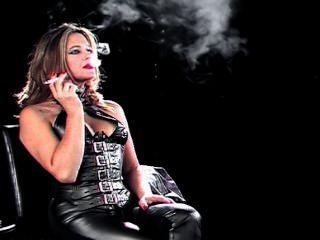 तंग चमड़े की पैंट और कोर्सेट में उमस भरे धूम्रपान लड़की