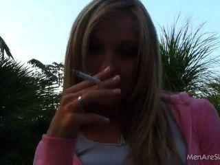 सुनहरे बालों वाली लड़की धूम्रपान आउटडोर