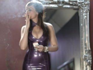 महिला बैंगनी लेटेक्स ड्रेस में मजबूत सिगरेट धूम्रपान