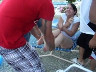 गर्म लड़की जूते और मोजे हटा दिया है और पूल में फेंक दिया हो