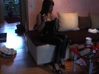 तंग चमड़े की पतलून, कोर्सेट और ऊँची एड़ी के जूते में धूम्रपान।अविश्वसनीय
